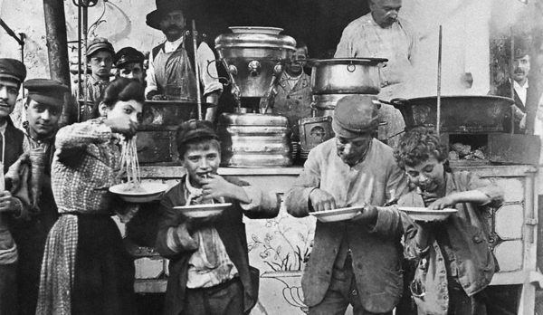 Children eating pasta from a street vendore, Italy 1930's